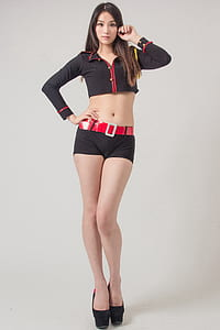 woman in black-and-red 2-button long-sleeved crop-top and black belted shorts