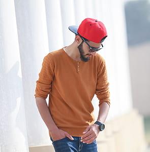 man wearing orange long-sleeved shirt and red cap