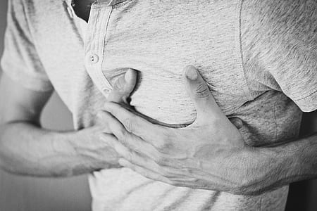 man holding chest grayscale photo