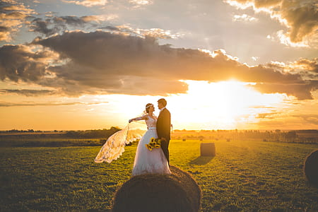 bride and groom taking picture on pale of hay under horizon