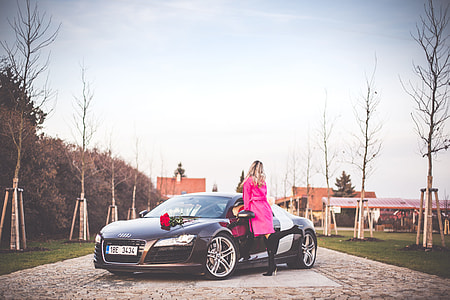 Woman in Pink Coat Standing Next To a Supercar
