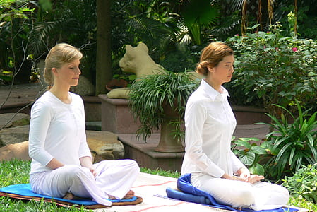 two woman in white long-sleeved top and pants sitting on mat outside during daytime
