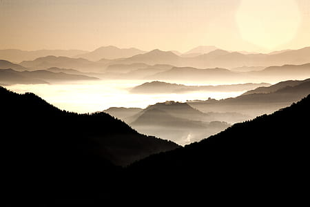 silhouette of mountain under clouds at daytime