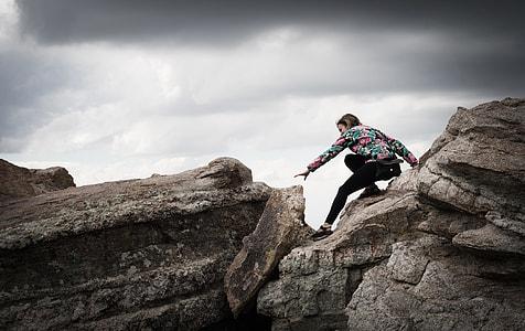 woman in black pants climbing rocks