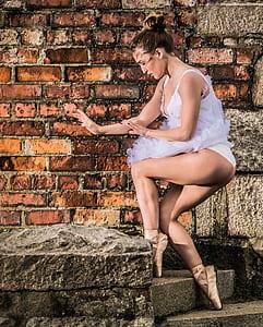woman wearing white spaghetti strap dress dancing on concrete pavement