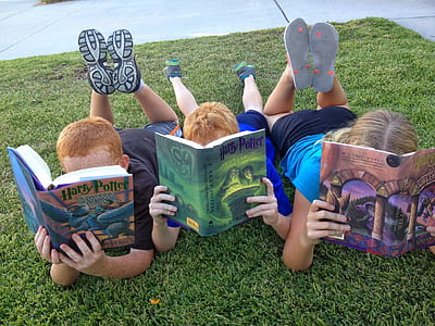 three childrens holding Harry Potter books while laying on grass photograph