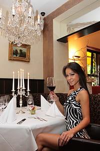 woman wearing white and black zebra-print sleeveless dress holding wine glass