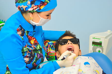 dentist checking boy's teeth wearingblack sunglasses