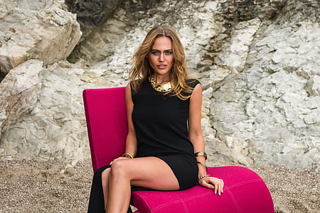 woman sitting on pink chair