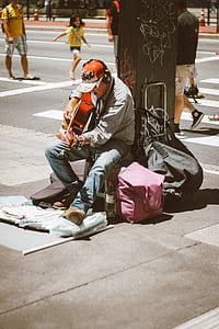 man playing guitar on street during daytime