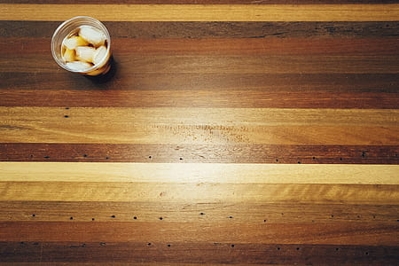 disposable cup on brown wooden flooring