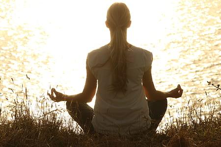 woman meditating near body of water