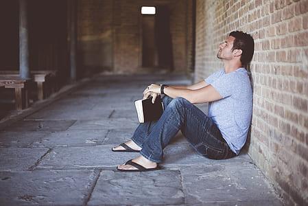 man wearing gray shirt holding book sitting beside brick wall