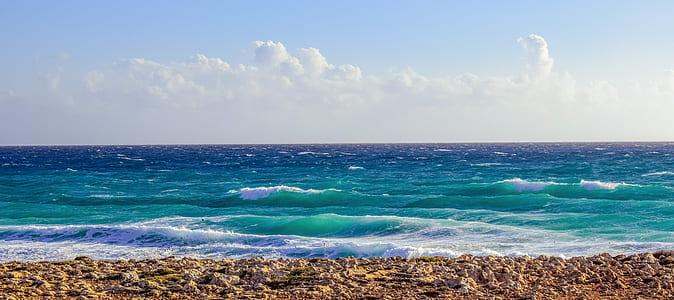 blue ocean under cloudy sky