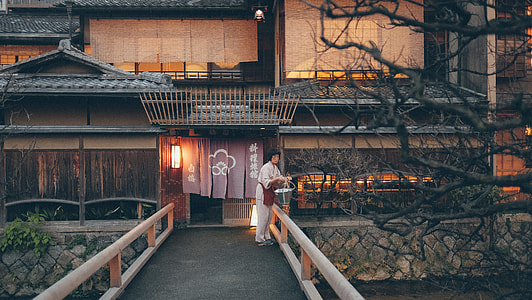 Japanese wooden house with woman in white clothes near river and bridge