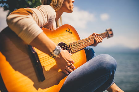 woman wearing sweatshirt playing acoustic guitar