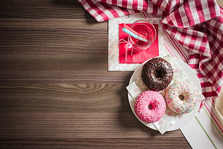 three doughnut place on white ceramic plate beside clear glass cup filled with water