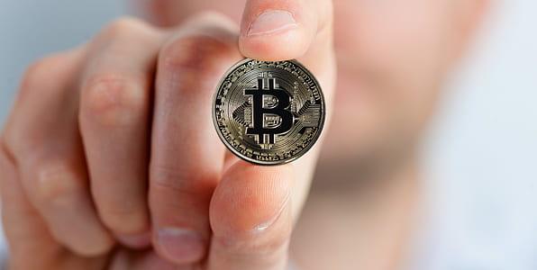 person holding Bitcoin coin