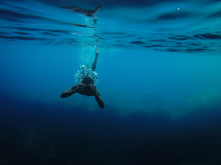 man diving on calm body of water
