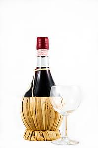 Clear Wine Glass Beside Red Wine Bottle