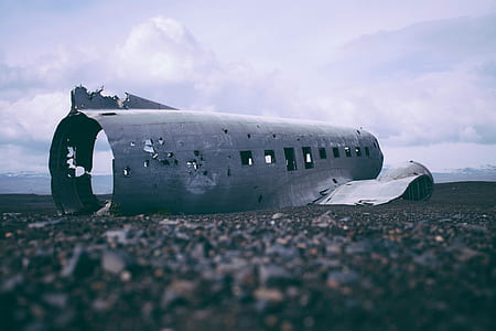 gray wrecked airliner on ground