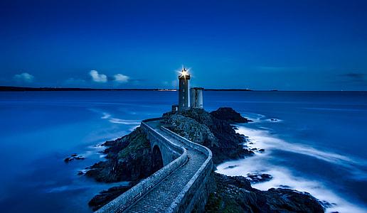 photo of lighthouse near sea