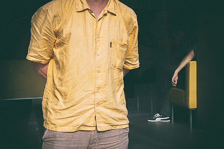 Cropped image of a man dressed in a yellow shirt. Image captured in Linz, Austria