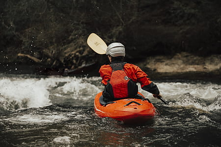 man wearing gray helmet kayaking on flowing stream