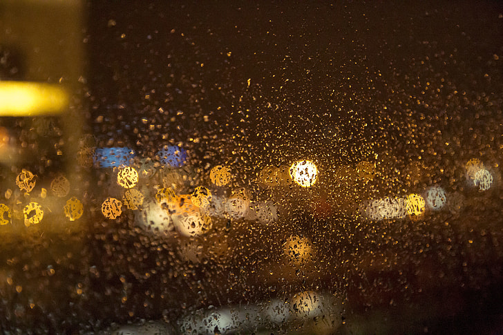 bokeh photography of water droplets on glass window