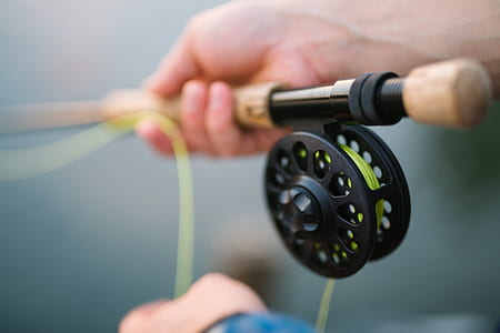 shallow focus photography of a person holding brown fishing rod