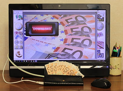 wallet with banknotes near flat screen computer monitor turned on