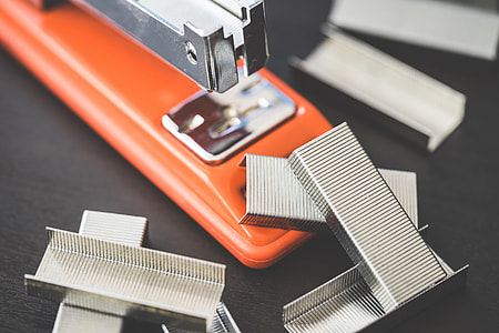 Red Office Stapler and Pile of Copper Office Staples