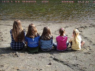 five girls sitting on seashore