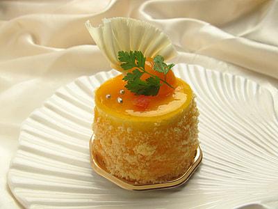 yellow cake on white shell shape ceramic plate