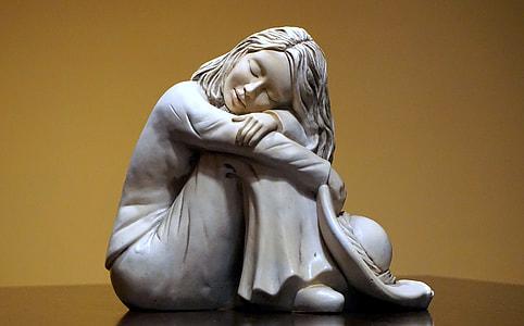 white ceramic statue of sleeping woman