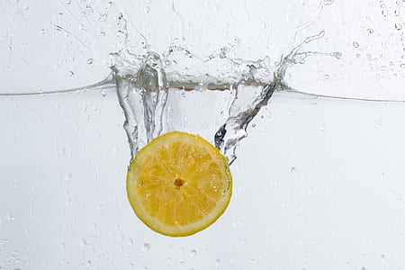 underwater photo of sliced lemon drop in water
