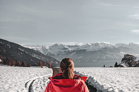 woman wearing red hoodie jacket standing in front of mountain
