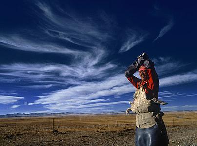 man wearing red suit standing outside below blue sky