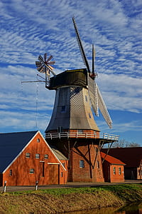 gray windmill beside brown house