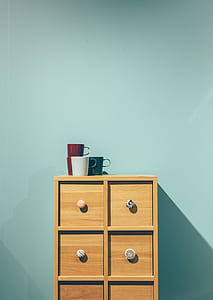 red, green, and white ceramic mugs on top of brown wooden dresser