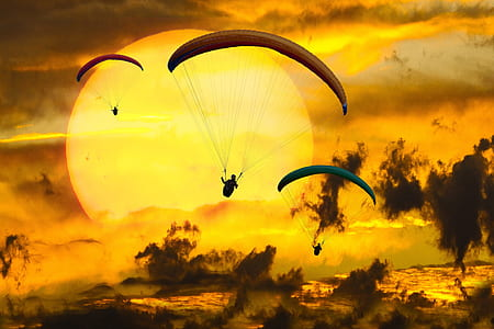three person parachute against sun