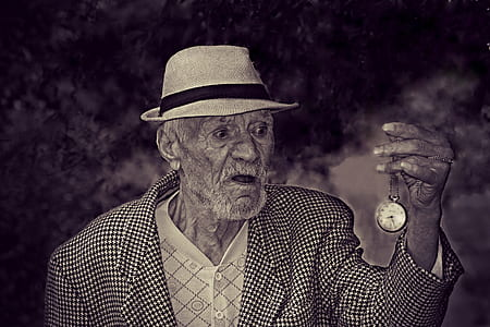grayscale photo of man holding pocket watch