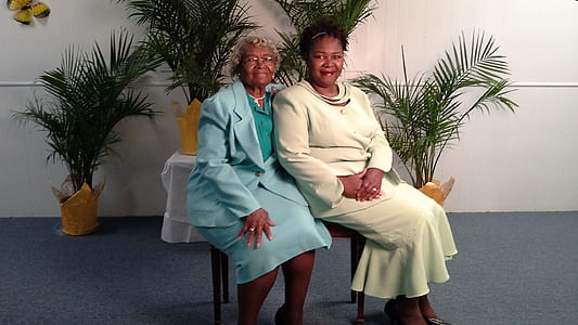 two women in blue and white dresses sitting on brown chair
