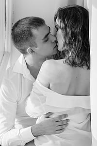grayscasle photo of woman and man kissing
