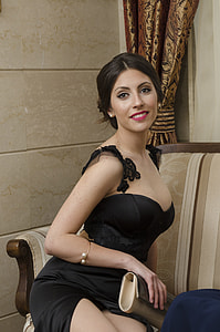 woman in black sweetheart dress sitting in room with brown walls