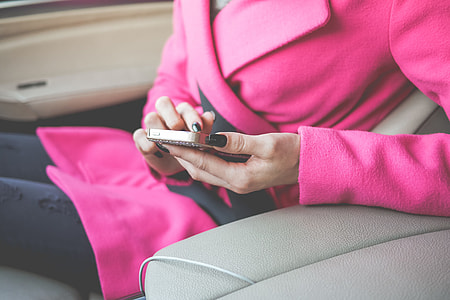 Nicely Dressed Woman Using Her Phone in a Car