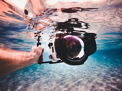 underwater photography of person holding white camera