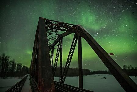 photography of bridge during green sky phenomenon