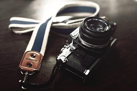 black camera on black surface with lanyard
