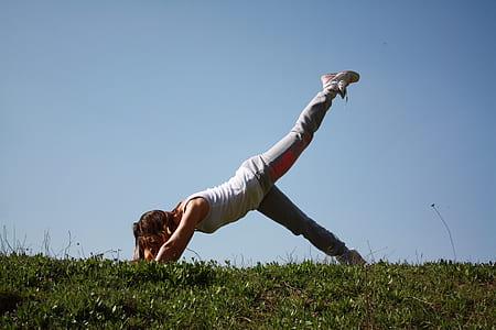 woman bending on green field